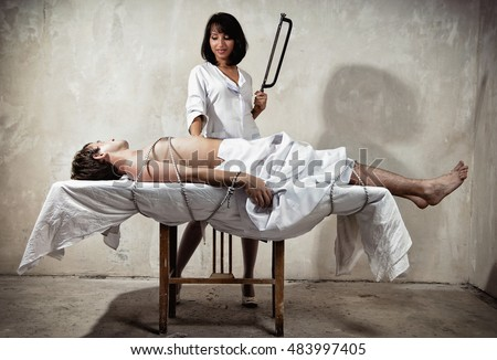 Man tied to a table and sexy woman in nurse uniform with a saw