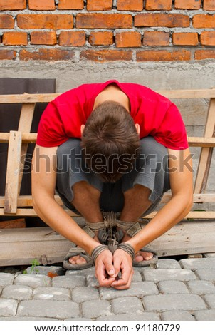 Man tied up with rope against break wall - stock photo