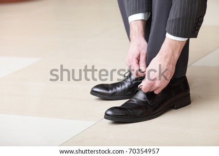 Man ties his shiney new black leather business shoes. - stock photo