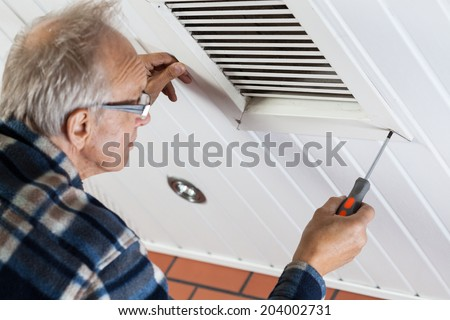 Man tightening the bolts on ventilation grille, horizontal