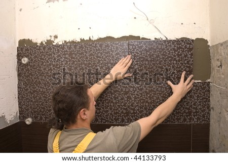 Man tiling a wall in the bathroom - stock photo