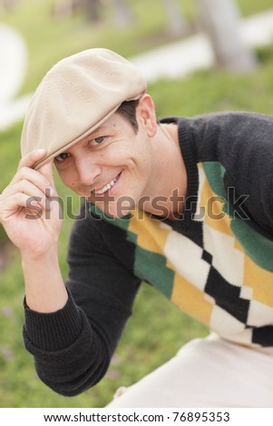 Man tipping his hat and smiling - stock photo