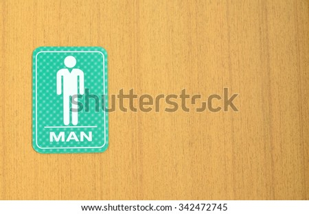 Man toilets sign for public restroom on a wood wall. - stock photo