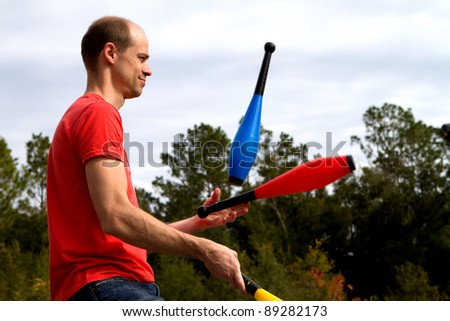 Man tosses and juggles pins in the air at a performance. - stock photo