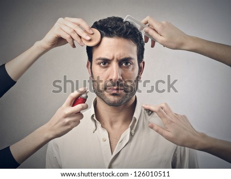 Man touched by four female hands - stock photo