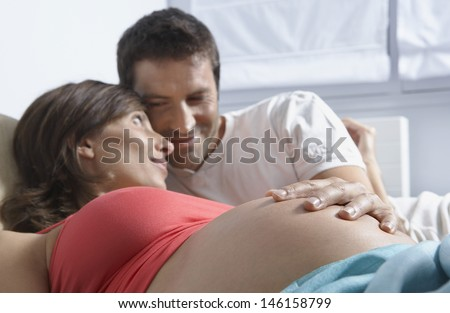 Man touching stomach of pregnant woman in bed at home - stock photo