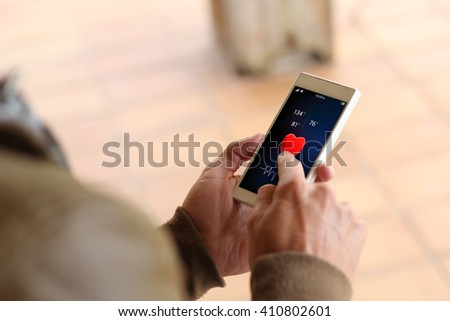 man touching the screen of his smartphone showing health app. All screen graphics are made up. - stock photo