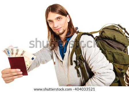 Man tourist backpacker holding passport full of money. Young guy hiker backpacking. Summer vacation travel. Isolated on white background. - stock photo