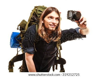 Man tourist backpacker taking photo picture with camera. Young guy hiker backpacking. Isolated on white background. - stock photo