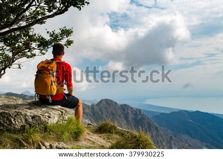 Man tourist hiker or trail runner looking at beautiful inspirational landscape in high mountains. Male runner with backpack, happiness and enjoying inspiring view on rocky top of mountain, Italy. - stock photo