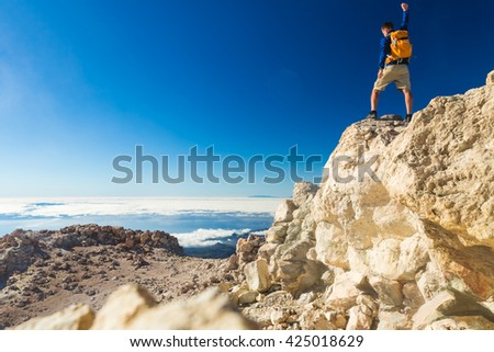 Man tourist hiker or trail runner looking at beautiful inspirational landscape in mountains. Fit runner with arms outstretched, happiness freedom and enjoy inspiring view on rocks top of Tenerife.