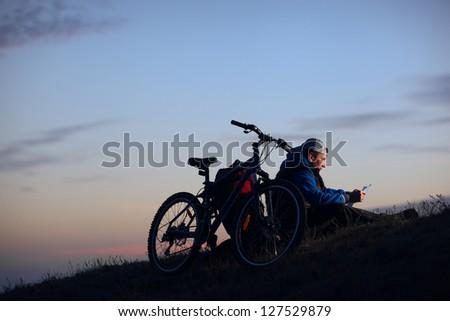 Man tourist on a bike sitting and studying a map at night. - stock photo