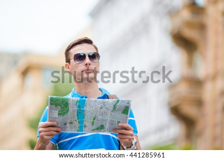 Man tourist with a city map and backpack in Europe. Caucasian boy looking at the map of European city in search of attractions. - stock photo
