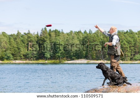 Man train his retriever by throwing a dummy - stock photo