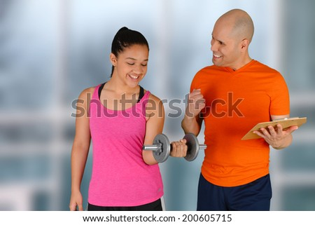 Man training girl working out while at the gym - stock photo