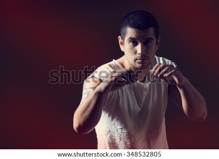 Man training in boxing gym. Dogfight the best method of self-defense. Young man holding hands in front of a position to defend and attack during a fight. Concept for  advertising hall of martial arts.