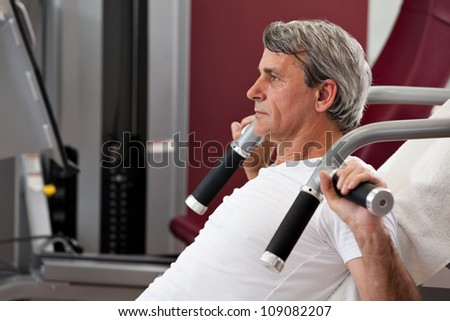 man training in the gym, smiling, leverage shoulder press