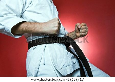Man training karate over red background - stock photo