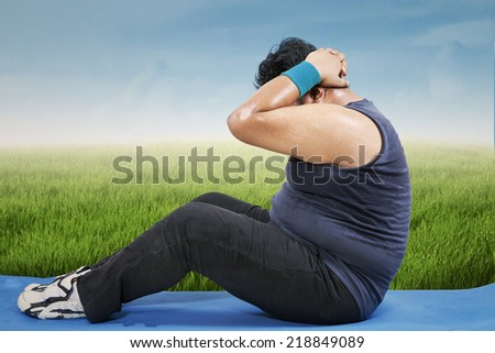 Man training on mattress to lose weight on the field, shot outdoors - stock photo