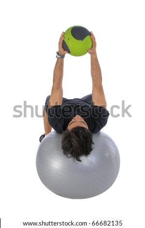 Man training with a weight medicine ball, lying horizontally balanced over a fitball - stock photo