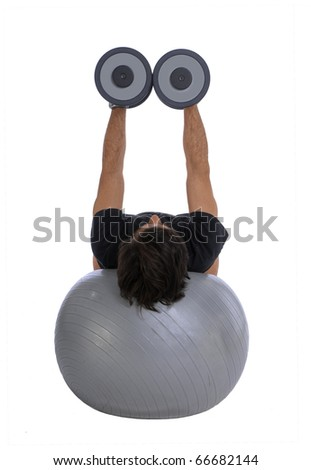 Man training with dumbbells, lying horizontally balanced over a fitball - stock photo
