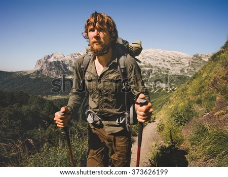 Man Traveler bearded with backpack hiking Travel Lifestyle concept mountains on background Summer vacations activity outdoor