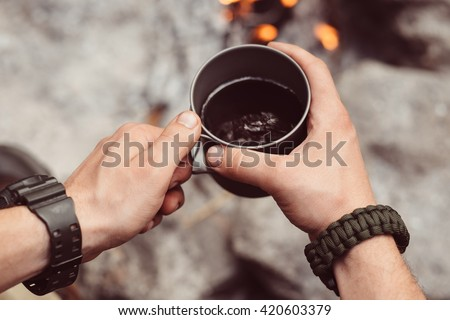 Man traveler hands holding cup of tea near the fire outdoors. Adventure, travel, tourism and camping concept. Hiker drinking tea from mug at camp. Coffee cooked over a campfire on the nature. - stock photo