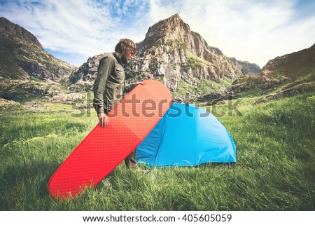 Man Traveler holding red mattress camping equipment and tent outdoor Travel Lifestyle concept rocky mountains landscape on background Summer adventure vacations  - stock photo