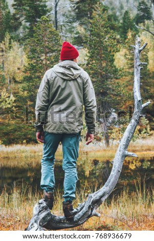 Man traveler in coniferous forest Travel lifestyle concept survival into the wild vacations wearing red hat