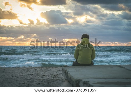 Man Traveler relaxing alone on beach seaside with sea waves and sunset sky on background summer vacations Travel Lifestyle concept - stock photo