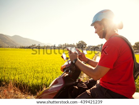 man traveler sitting on a motorbike and exploring the route map. Away rice fields. Vietnam. - stock photo