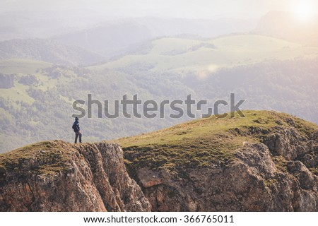 Man Traveler standing on mountain cliff outdoor Travel Lifestyle concept Summer vacations journey - stock photo