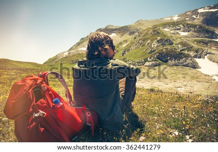 Man Traveler with backpack relaxing outdoor Travel Lifestyle concept mountains on background Summer vacations - stock photo