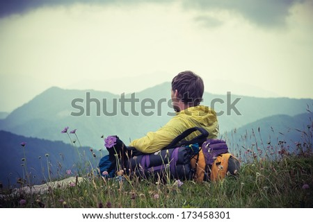 Man Traveler with backpack relaxing with Mountains on Background Summer Traveling Outdoor - stock photo