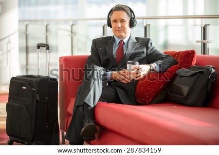 Man traveling alone on business trip listens to music patiently - stock photo