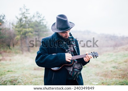 man traveling with a guitar - stock photo