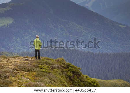 Man travels through the mountains! Enjoy beautiful views of the mountains! Summer holidays in the mountains! Travel through the mountains with a backpack and tents - stock photo