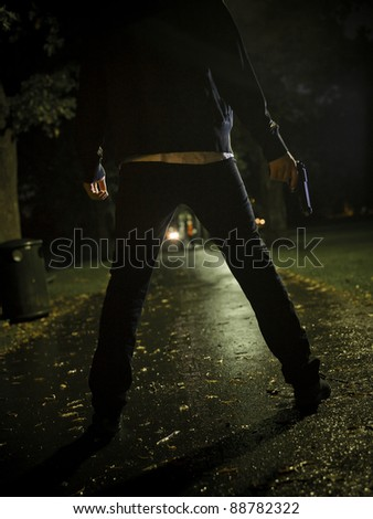 Man treating two women with a gun at night - stock photo