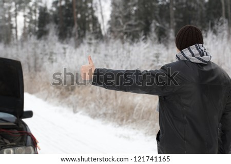 Man tries to stop a car on a country road - stock photo