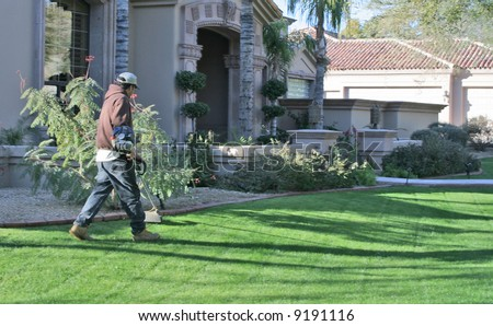 man trimming edges of grass at upscale home - stock photo