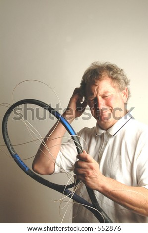man trying to figure out how to string his tennis racket - stock photo