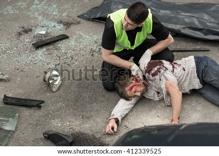 Man trying to help injured bomb explosion victim lying on street. - stock photo