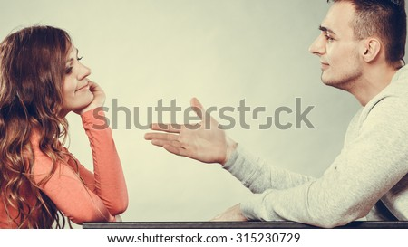 Man trying to reconcile with woman. Couple making up after quarrel. Husband reaching out to wife. Instagram filtered. - stock photo