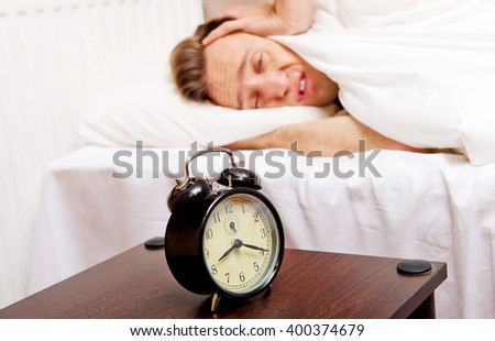 Man trying to sleep, when alarm clock ringing - stock photo