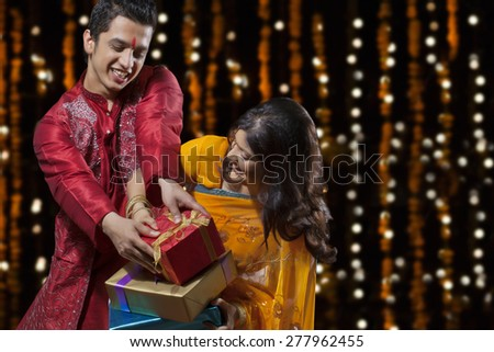 Man trying to snatch gifts from woman - stock photo