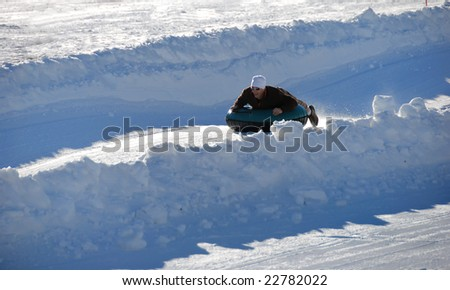 man tubing fast down the hill with snow background - stock photo