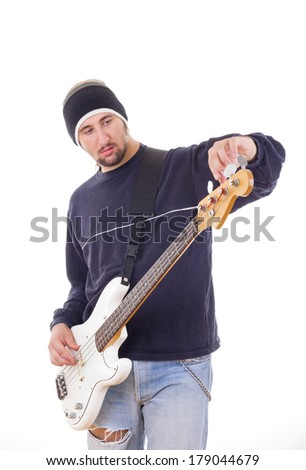 man tuning a guitar with adjustments, wearing sweatshirt and jeans
