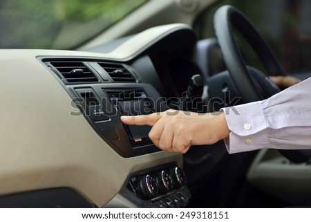 Man Turn On Radio While Driving. Automotive concept image - stock photo