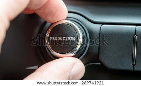 Man turning a dial or electronic control knob with the word Production on the top in a conceptual image. - stock photo