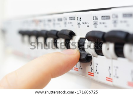 man turning off the fusebox - stock photo
